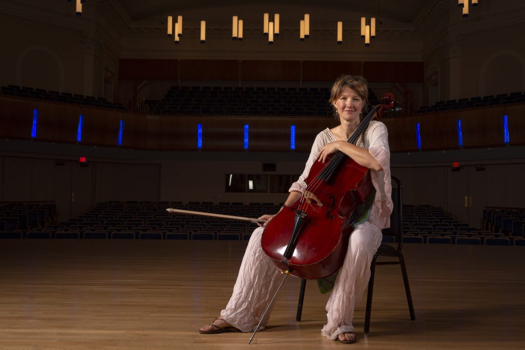 Caroline Stinson sits with her cello for a portrait in Baldwin Auditorium