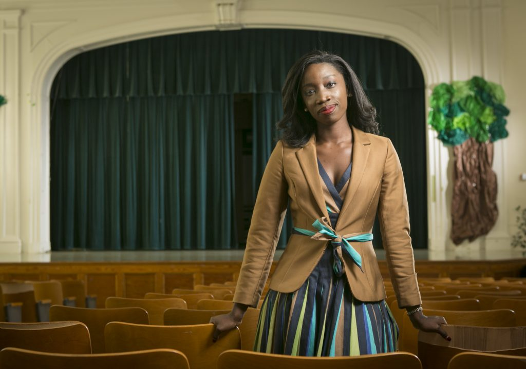 Sally Nuamah, assistant professor in the Sanford School of Public Policy, poses for a photo in the auditorium at E.K. Powe Elementary School in Durham.