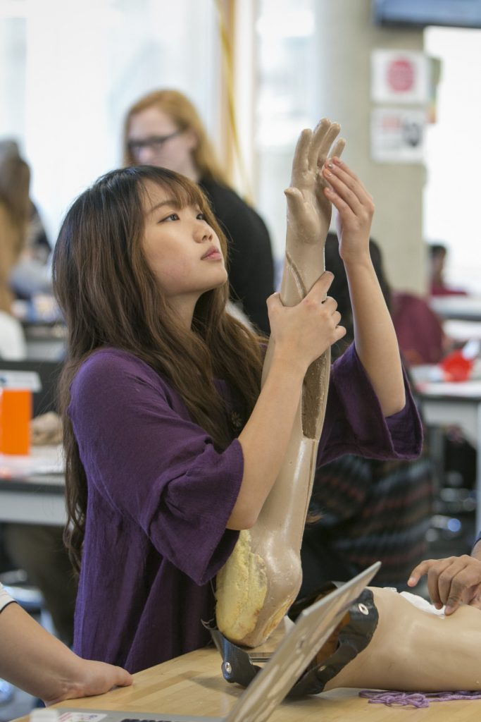 An engineering student inspects her work on a prosthetic arm at the Pratt Design Pod