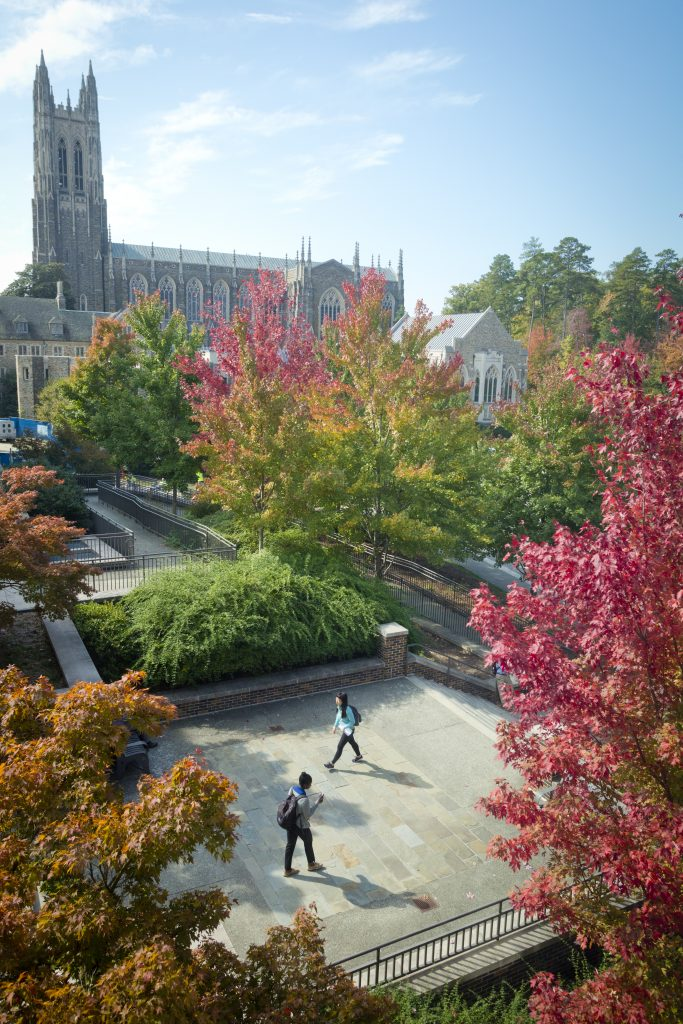 Students walk across the Bostock Library plaza as the Chapel is visible in the distance above the colorful fall trees.