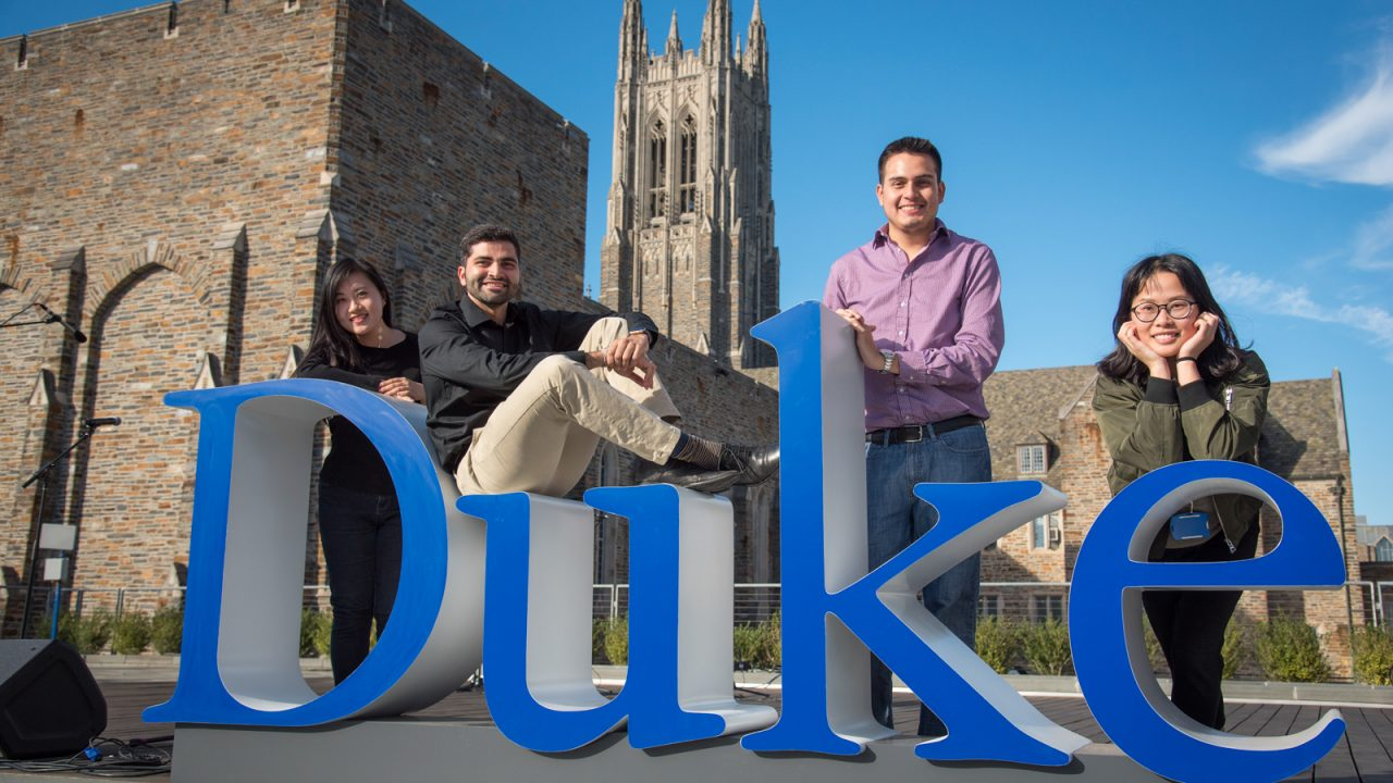 Four students pose for a photo next to a giant 3-D cutout of the Duke wordmark.