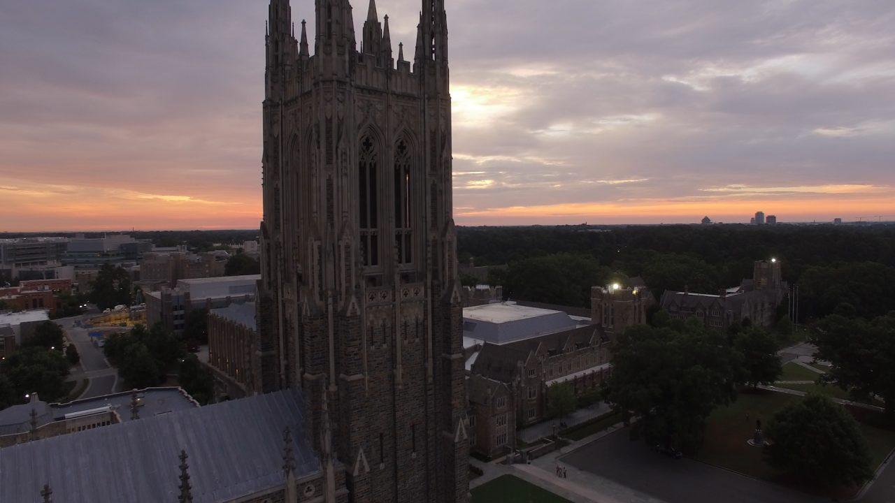Aerial still of the sun rising over Duke Chapel